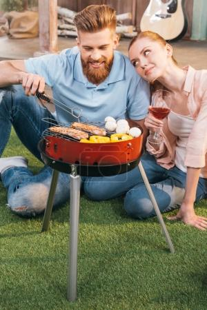 Couple grilling meat and vegetables