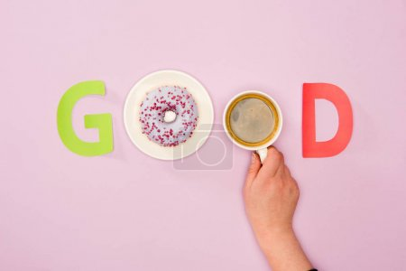 Photo for Top view of Good word made from and cup of coffee in human hand and donuts isolated on pink. donuts and coffee background - Royalty Free Image