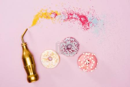 Photo for Top view of three frosted donuts and golden bottle on pink surface. Colorful donuts chocolate background - Royalty Free Image
