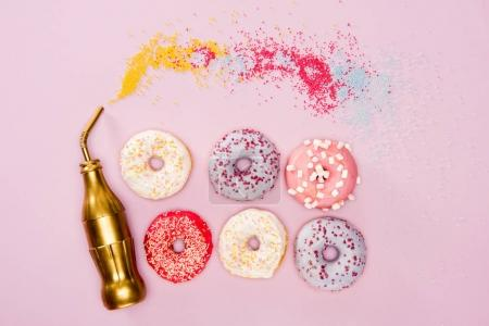 Photo for Top view of variety frosted donuts and golden bottle on pink surface. donuts chocolate background - Royalty Free Image