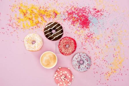 Photo for Top view of donuts with different sweet glaze, sprinkles and cup of coffee on pink. Donuts chocolate background - Royalty Free Image