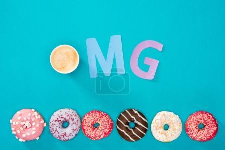 Photo pour Vue aérienne de tasse à café, signe OMG et beignets sucrés isolés sur bleu. Fond appétissant beignets cuits au four - image libre de droit