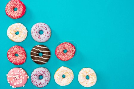 Photo for Overhead view of colorful donuts isolated on blue. Appetizing background of donuts in minimalist style - Royalty Free Image