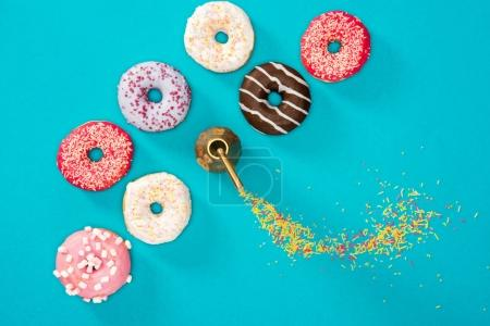 Photo for Overhead view of food composition with several donuts with various glaze on blue. Sweet background of donuts - Royalty Free Image
