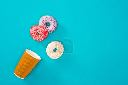 Photo for Overhead view of scattered donuts with various glaze. sweet donuts isolated on blue. Sweet background of donuts. - Royalty Free Image