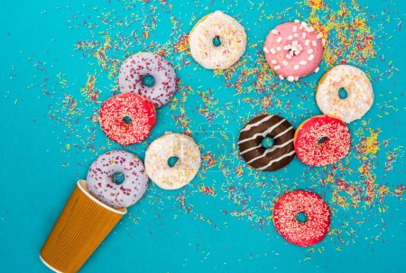 Photo for Overhead view of scattered several donuts with various glaze. donuts isolated on blue background - Royalty Free Image