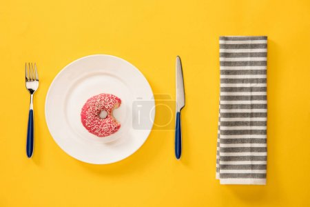 Foto de Vista aérea de buñuelo mordido con esmalte rosa en plato y servilleta aislado sobre fondo amarillo. Fondo estilo minimalista - Imagen libre de derechos