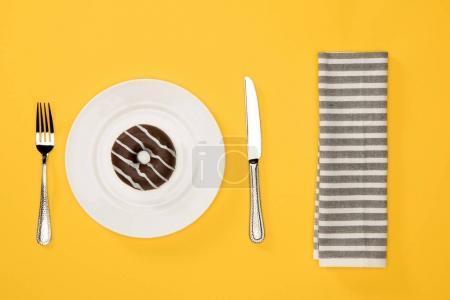 Foto de Vista aérea de donut glaseado dulce en plato y servilleta aislado sobre fondo amarillo. Fondo de donuts de chocolate estilo minimalista - Imagen libre de derechos