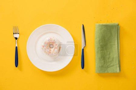 Foto de Vista aérea de donut glaseado dulce en placa y verde servilletas aislado sobre fondo amarillo. Fondo estilo minimalista - Imagen libre de derechos