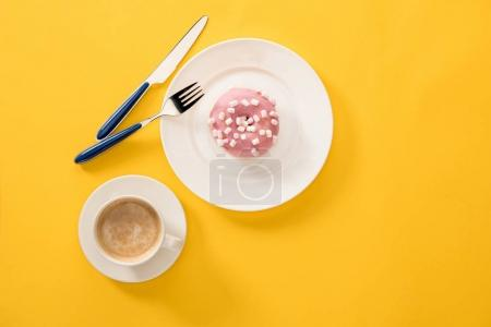 Photo for Top view of cup of coffee with donut topped by pink frosting on yellow surface. donuts and coffee isolated on white background - Royalty Free Image