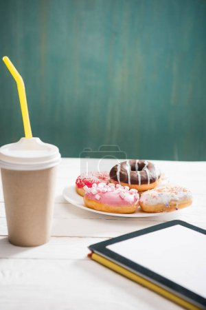 Photo for Unhealthy breakfast with coffee to go, plate of frosted donuts and digital tablet with white screen on wooden table. donuts and coffee background - Royalty Free Image