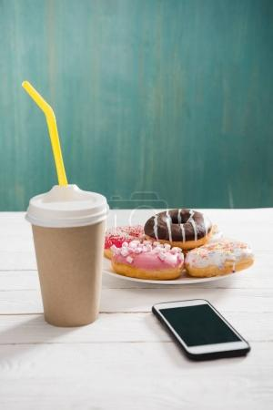 Photo for Unhealthy breakfast with coffee to go, plate of frosted donuts and smartphone wth black screen on wooden table. donuts and coffee background - Royalty Free Image