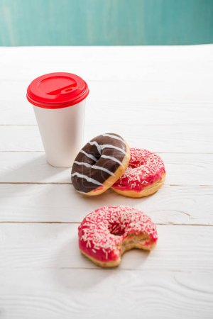 Coffee cup and three donuts