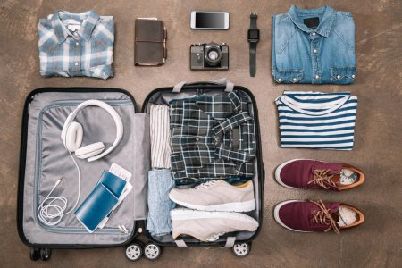 Photo for Top view of an essential vacation items in open luggage with digital devices on wooden background - Royalty Free Image