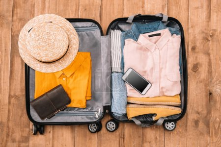 Photo for Top view of open luggage full of clothes, document and smartphone on wooden floor, Summer travel concept - Royalty Free Image