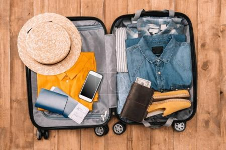 Photo for Ready for travel concept. Top view of essentials for tourist with clothes, accessories and gadgets, wallet, passport, smartphone in bag. - Royalty Free Image