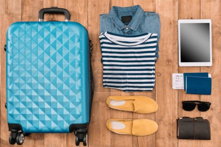 Photo for Flat lay with luggage, male clothes, accessories and digital tablet on wooden floor. Ready for travel concept - Royalty Free Image