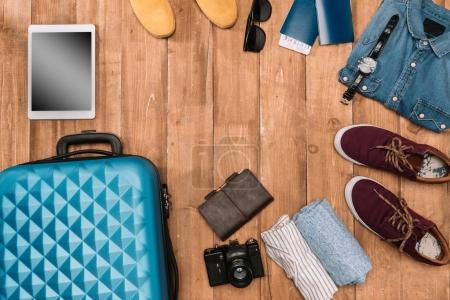 Photo for Summer vacation background with travel accessories. closed luggage, shoes, digital devices and passports on wooden floor. - Royalty Free Image