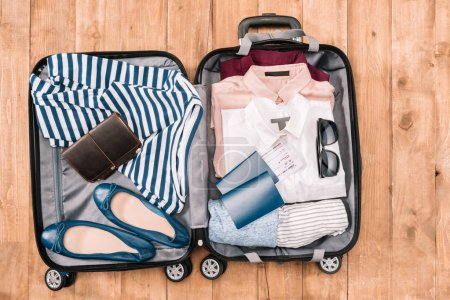 Photo for Overhead view of traveler's accessories and clothes organized in open luggage on wooden floor - Royalty Free Image