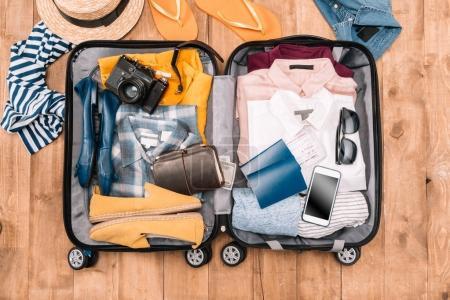 Photo pour Vue aérienne des accessoires de voyage organisés en bagages ouverts sur sol en bois - image libre de droit