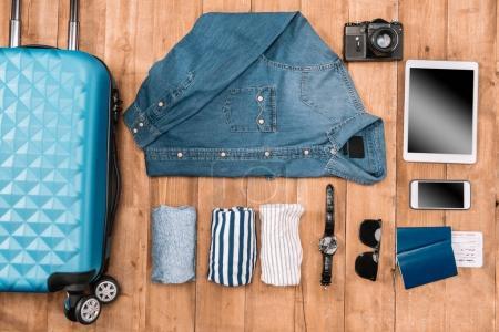 Photo pour Pose flay du concept de vacances d'affaires avec vêtements, smartphone, passeport et billets sur le sol en bois . - image libre de droit