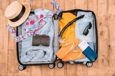 Photo for Top view of open luggage full of woman's clothes and other essential vacation items. Ready to summer vacation - Royalty Free Image