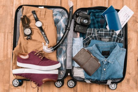 Photo for Top view of open luggage full of men clothes, gadgets, and other essential vacation items. Ready to summer vacation - Royalty Free Image