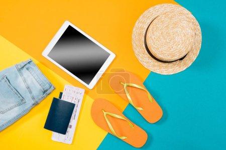 Foto de Vista superior de naranja ojotas, pasaportes, billetes, tableta digital y ropa de colores de fondo. Elementos esenciales de vacaciones, Fondo de concepto de viaje - Imagen libre de derechos