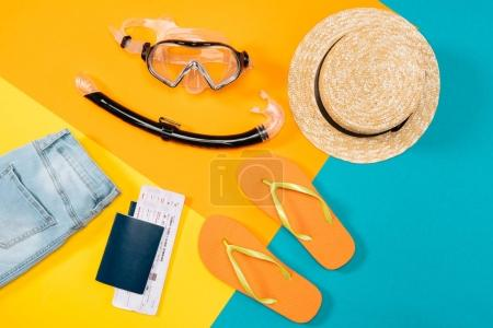 Photo for Overhead view of clothes, flip flops, tickets, headphones, smartphone and snorkeling equipment on colored background. Ready for summer vacation - Royalty Free Image