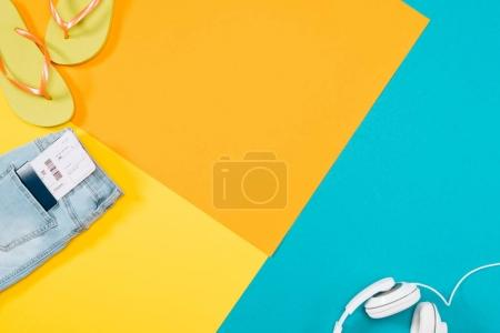 Photo for Summer vacation background with headphones, flip flops, denim trousers, ticket, passport with copy space - Royalty Free Image
