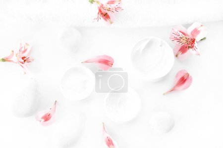 Photo for Top view of pink orchid flowers with petals and organic cream in containers - Royalty Free Image