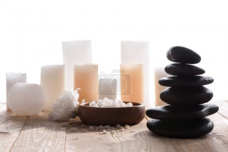 Photo for Close-up view of piled spa stones and candles with sea salt on wooden table top - Royalty Free Image