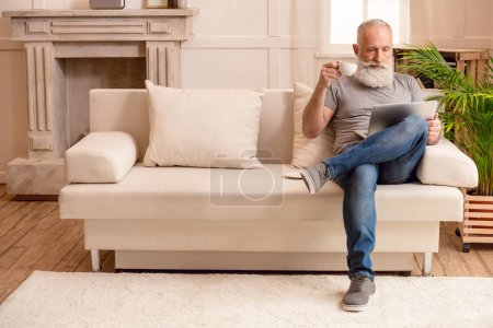 Photo for Senior bearded man drinking coffee and looking on laptop while sitting on sofa at home - Royalty Free Image