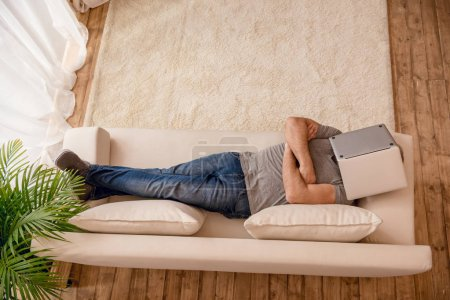 Photo for Top view of man with crossed arms relaxing on sofa with laptop on his fase - Royalty Free Image
