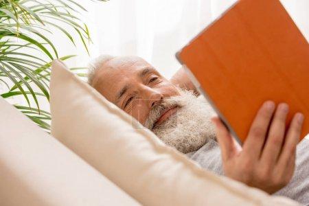 Photo pour Heureux homme barbu senior en utilisant une tablette numérique et couché sur le canapé à la maison - image libre de droit