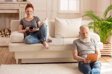 Photo for Husband using digital tablet and sitting on floor while wife using smartphone and sitting on sofa - Royalty Free Image