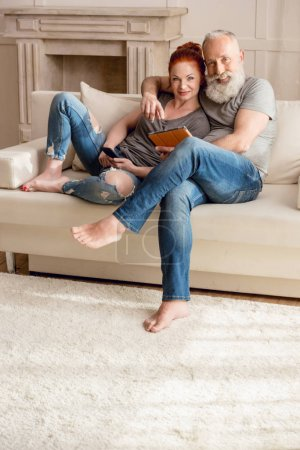 Photo for Beautiful mature couple sitting on sofa with digital devices and smiling at camera - Royalty Free Image