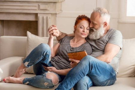 Photo for Beautiful mature couple sitting embracing and using digital tablet - Royalty Free Image