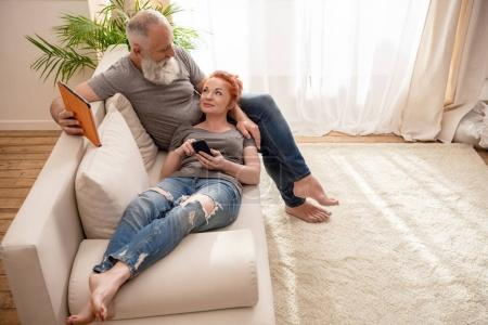 Photo pour Beau couple mature tenant des appareils numériques et se souriant à la maison - image libre de droit