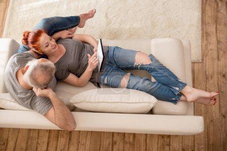 Photo pour Vue aérienne du couple mature heureux en utilisant une tablette numérique sur le canapé - image libre de droit