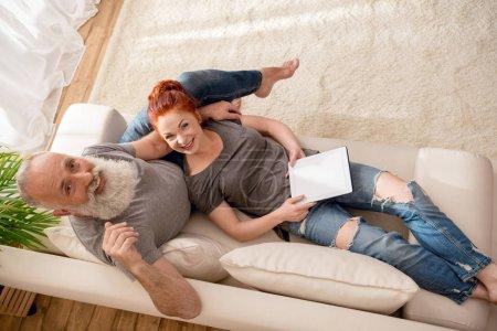 Photo pour Vue grand angle du couple mature heureux à l'aide d'une tablette numérique et souriant à la caméra - image libre de droit