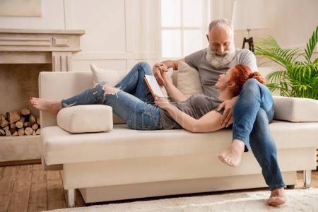 Photo pour Heureux couple mature en utilisant tablette numérique ensemble à la maison - image libre de droit