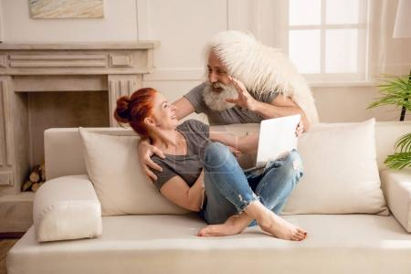 Photo for Happy mature couple using laptop and having fun together at home - Royalty Free Image