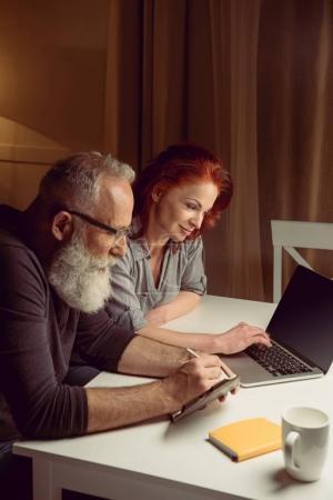 Photo pour Couple d'âge moyen travaillant sur ordinateur portable tout en étant assis à la table - image libre de droit