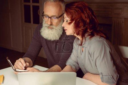 Photo pour Couple d'âge moyen regardant ordinateur portable tout en étant assis à la table près d'un ordinateur portable - image libre de droit