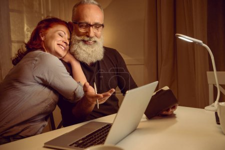 Middle aged couple sitting near laptop