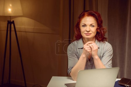 Photo for Mature red hair woman sitting at table near laptop and looking at camera - Royalty Free Image