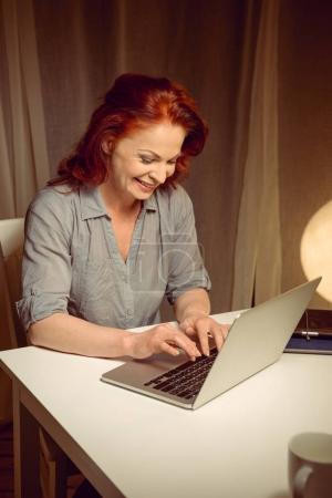 smiling mature woman working on laptop