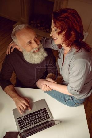 Photo pour Sourire couple d'âge moyen assis à la table et embrasser tout en utilisant un ordinateur portable à la maison - image libre de droit
