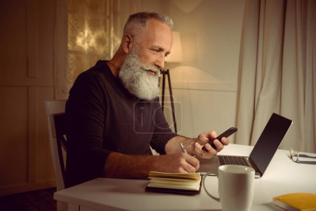 grey haired man working at home